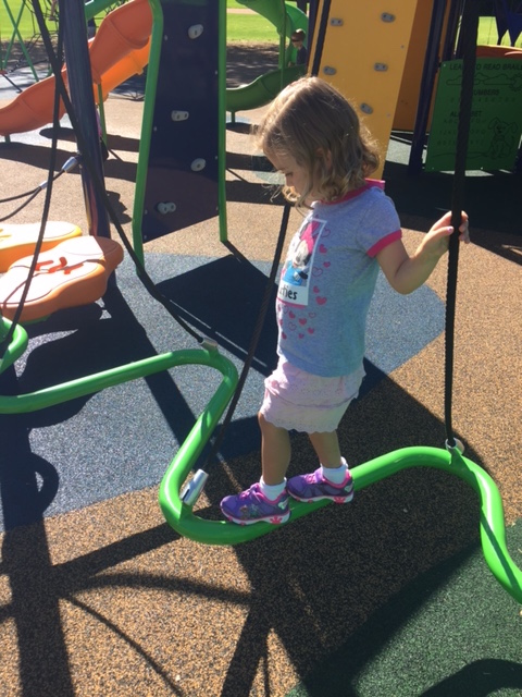 Erin's daughter balancing on the new playground equipment.