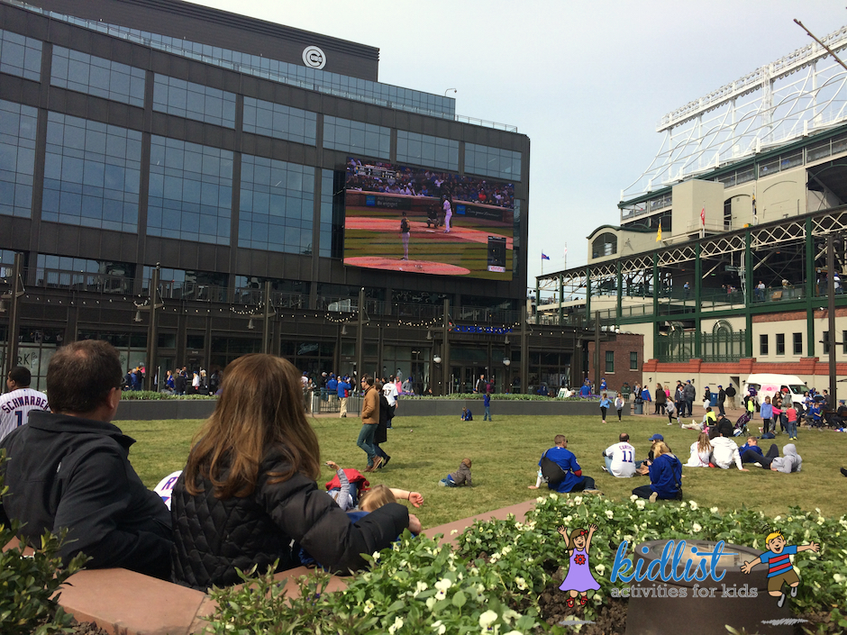The Park at Wrigley with an open, grassy field and big screen playing the Cubs game