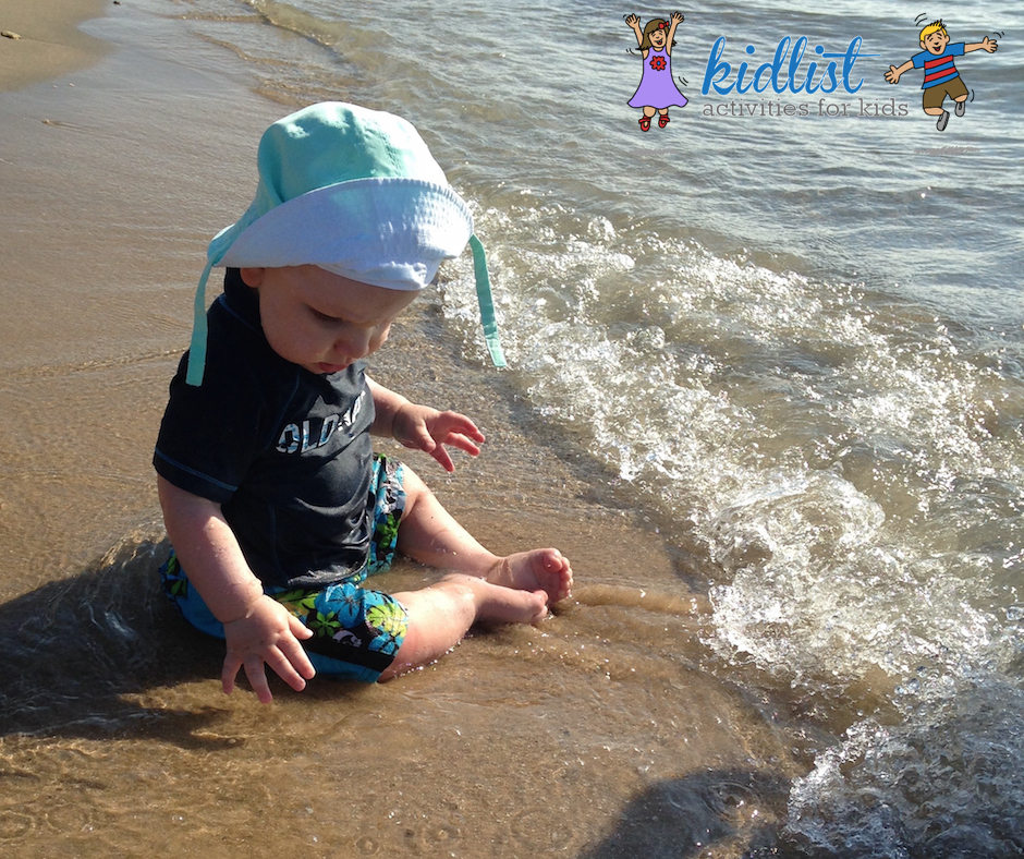 Baby sits on the beach as a wave rolls in
