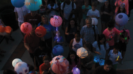 Glow in the Park event picture - people hold illuminated lanterns on sticks