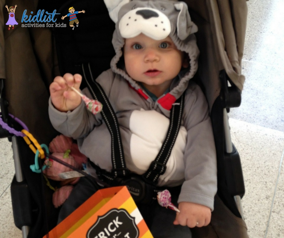 Child, dressed as a dog, holds candy at an indoor trick-or-treating event