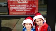 Two children in Santa hats stand in front of a toy drive collection sign