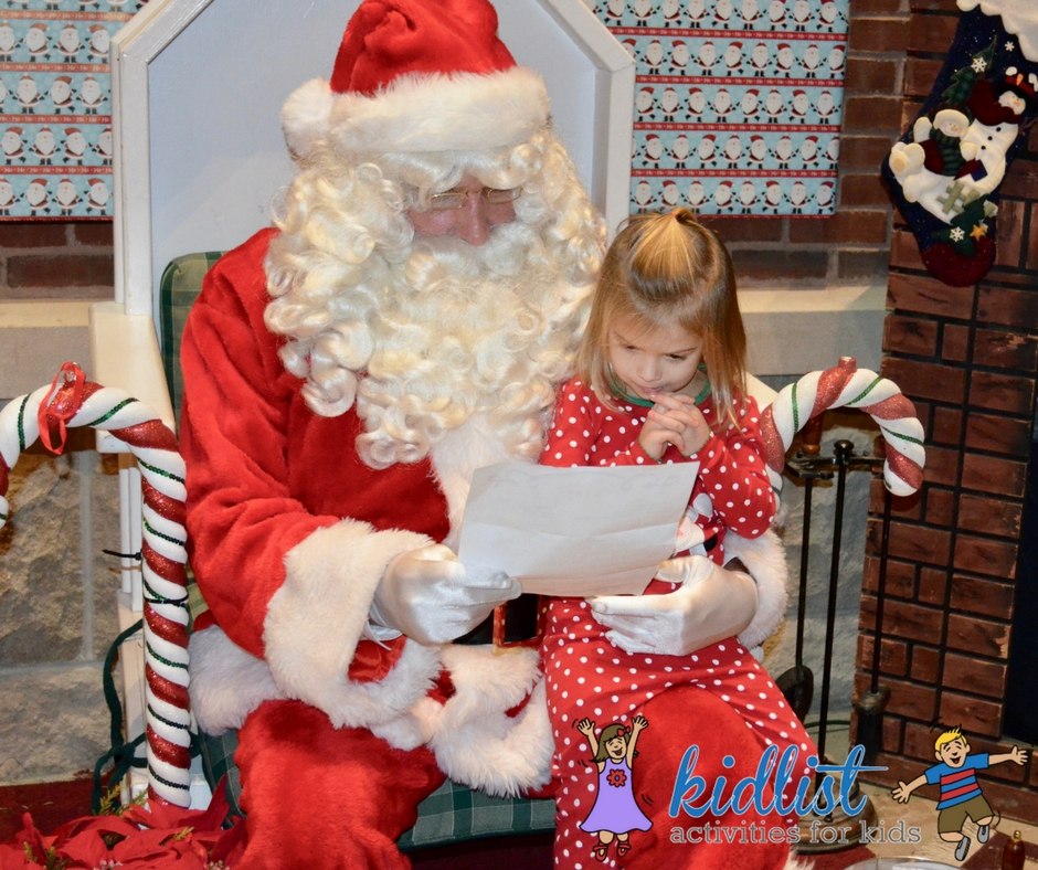 A child sits on Santa's lap to share her list